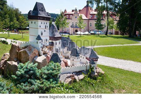 CZECH REPUBLIC, KUNICE - JUN 15, 2015: castle Berchtold from 1877 and park with model miniatures of czech landmarks, Benice, Vidovice village, Czech republic. Model of Karlstejn castle