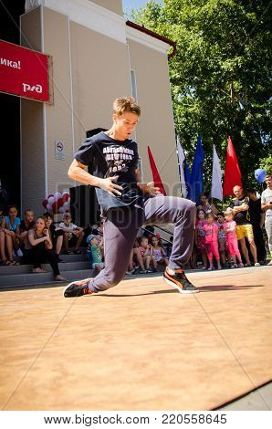 Komsomolsk-on-Amur, Russia, August 1, 2015. a boy dancing a break dance in the square with spectators