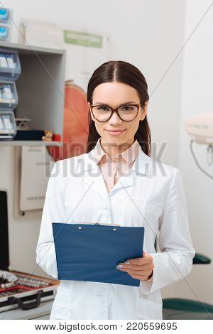 portrait of smiling optometrist in white coat with notepad in hands looking at camera