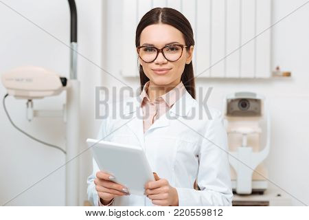 portrait of young optometrist with digital tablet in hands looking at camera in clinic