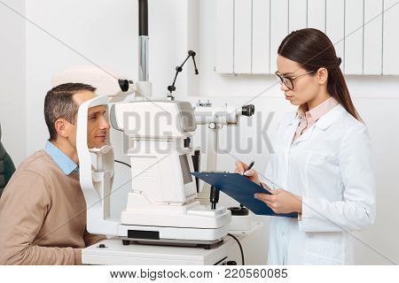 side view of patient getting eye examination in slit lamp in clinic