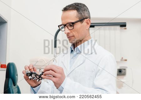 optometrist in white coat looking at trial frame in hands in clinic