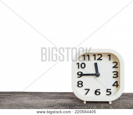 Closeup white clock show the time in a quarter to twelve o'clock or 11:45 a.m. on old brown wood desk isolated on white background with copy space