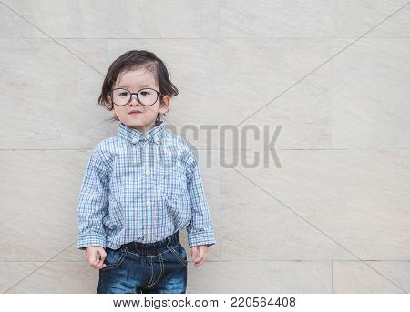 Closeup happy asian kid with eyeglasses in gentle kid concept on marble stone wall textured background with copy space
