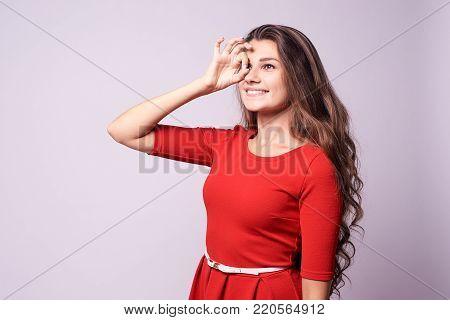 Gesture consent. Beautiful girl. White background. Portrait brunette.