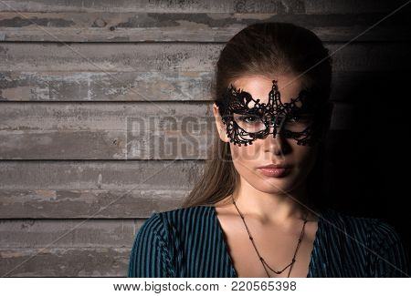 Horizontal closeup portrait of young beautiful lady in elegant masquerade mask. Face in the shadows. Black lace mask on the eyes. Professional makeup