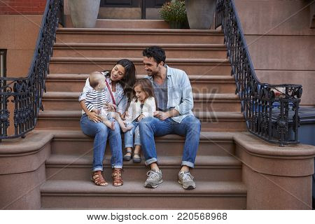 Young family with kids sitting on front stoops