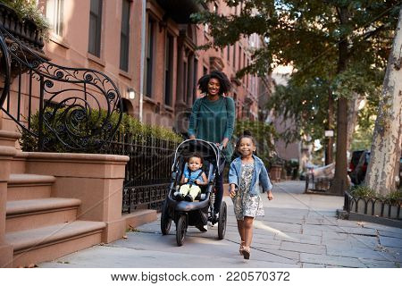 Mother and two daughters taking a walk down the street