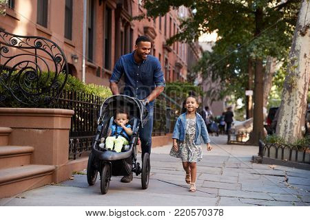 Father and two daughters taking a walk down the street