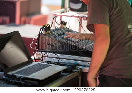 Sound Engineer works with Professional Sound System Mixing Audio Musical Equipment Board.