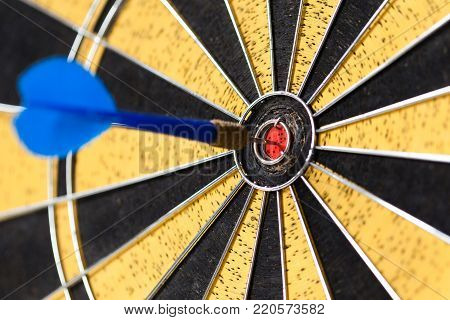 Successful mission concept. Dart board. Hitting target aim, goal achievement blue sting in bull's eye. Retro design sport game.