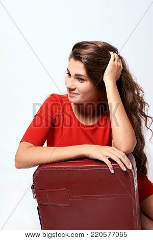 Pensive brunette. Journey. Girl with a suitcase.