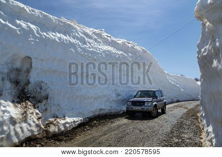 VILYUCHINSKY VOLCANO, KAMCHATKA PENINSULA, RUSSIA - JUNE 18, 2017: Japanese off-road car Mitsubishi Pajero iO on mountain road in snow tunnel surrounded by high snowdrifts on Vilyuchinsky Pass.