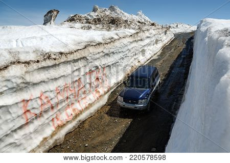 VILYUCHINSKY VOLCANO, KAMCHATKA PENINSULA, RUSSIA - JUNE 18, 2017: Japanese off-road car Mitsubishi Pajero iO driving on mountain road in snow tunnel surrounded by high snowdrifts on Vilyuchinsky Pass