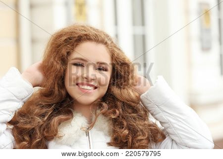 Beautiful smiling woman in jacket with faux fur collar outdoors