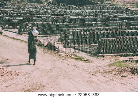 poor barefoot person carrying pitcher on shoulder and outdoor warehouse of bricks around in Nepal