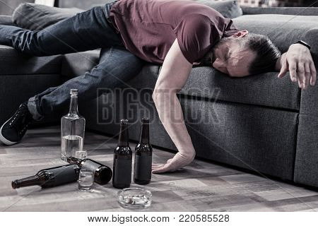 Alcohol addict. Sleepy drunk bearded man lying on the sofa and resting while thinking about alcohol