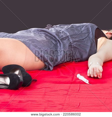 addict woman lies unconscious on the red bedsheet near a syringe