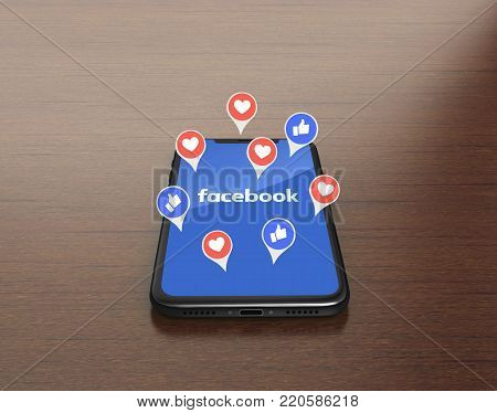Kiev, Ukraine - January 4, 2018: 3D Render of a black iPhone X with mobile application of Facebook on the screen with Empathetic Emoji