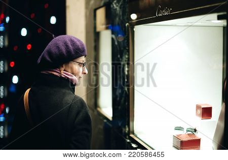 STRASBOURG, FRANCE - DEC 23, 2015: French elegant woman search for the Christmas gift in Cartier Jewelry shop from the French Street - searching for the best present during Christmas holidays