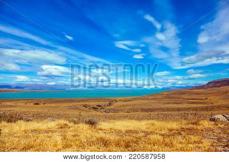 The concept of active and exotic tourism. Flat plain with shallow lake and yellowed grass. Patagonian Pampas. Strong wind carries clouds