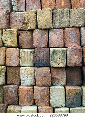 Close up of stacked terra-cotta bricks used for construction work.  A grunge brick block pattern.