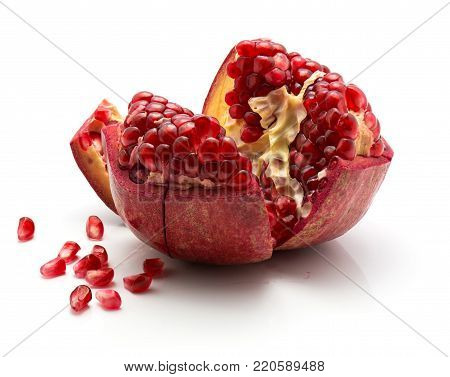 Open pomegranate with revealed grains isolated on white background