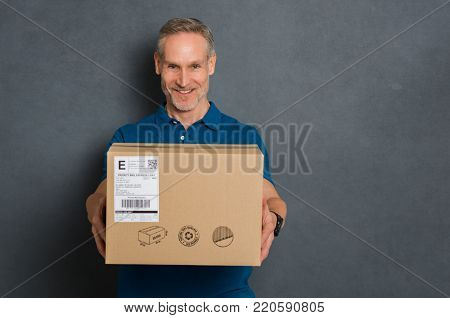 Happy delivery man stretching out his arms to give the package. Smiling courier giving card box on grey background. Portrait of deliveryman handing parcel to customer isolated with copy space.