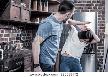 Self defense. Unhappy emotional young woman raising her hand up and trying to protect herself while having a fight with her husband