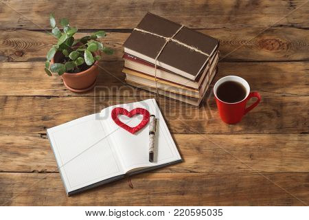 Disclosed Diary, Red Heart, Flower, Pile of Book, Red Cup with Coffee or Tea, Pen on a wooden Table. Symbol of Love, Knowledge.