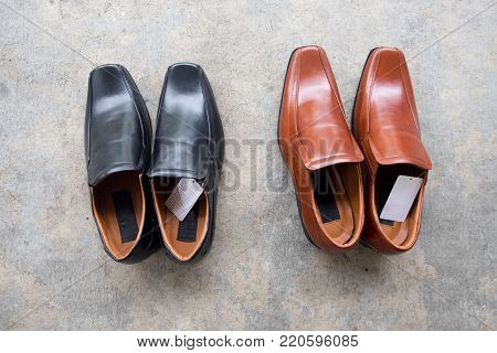 New black shoe and brown shoe made of leather, top view