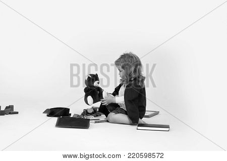Small boy child blond in black academic mantle sitting and play with teddy bear and squared cap surrounded by diaries wooden cubes box of colored pencils and car toys isolated on white background