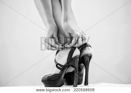 Black shoes female fancy high heel pumps strappy sandals on woman legs beautiful feet on white floor