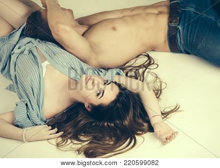 Woman with long in blue gown. Man with muscular torso in jeans. Relationship, family, lovers. Erotic, desire concept. Couple in love relax on white floor.