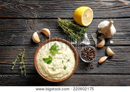 Tasty sauce with garlic in bowl and ingredients on wooden table