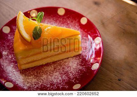 Tasty orange fruit cake on red christmas patt dish for ready to eat