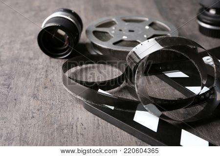 Filmstrip and movie clapper on grey background, closeup
