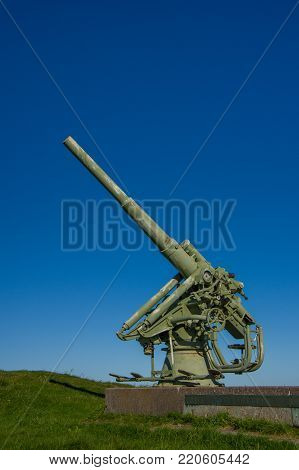 Anti-aircraft Gun On A Granite Pedestal, On The Background Of Blue Sky