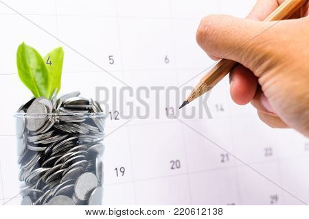 Plan to saving money in glass for your investment future is similar to growing green leaves on tree and write a message on calender for background or texture - economical & activity 2018 concept.