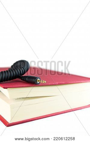 3.5 jack plug coming out of a book with red cover. Ebook concept, audio book concept or information technology