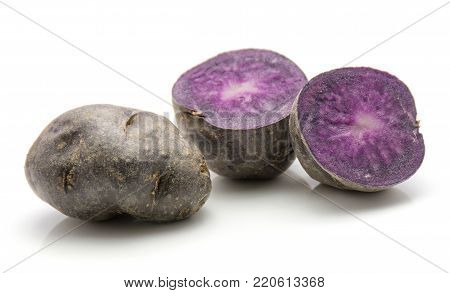 Vitelotte potatoes isolated on white background one whole and two sliced halves