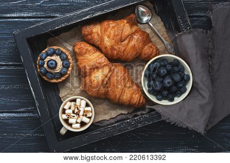 Croissants, cake with blueberries, coffee with marshmallows on a wooden tray with a napkin. Wooden dark background, top view