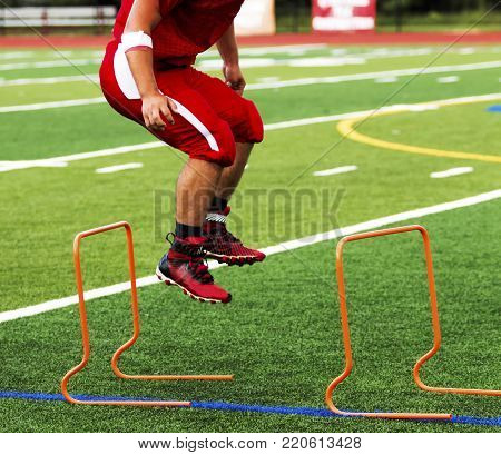 A high school football player jumping over orange hurdles during pre season practice on a gree turf field.