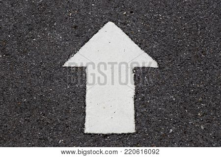 White painting in forward direction arrow symbol on black asphalt road background