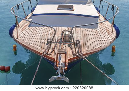Small sport fancy boat with wooden deck tied at marina dock