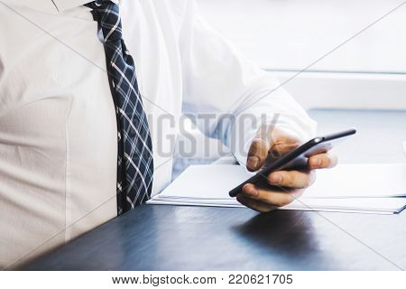 Businessman working with generic design notebook. Holding smartphone in hands. Horizontal, sunlight effects background