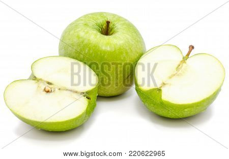 Sliced apple Granny Smith, one whole and two halves, isolated on white background