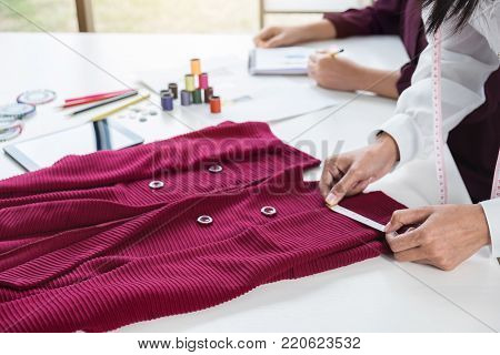 Two young dressmaker or designer colleagues working as fashion designers and drawing sketches for clothes, choose color bar in tablet, profession and job occupation, Fashion Designer Stylish Concept.