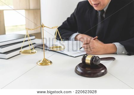Close up of gavel, Male lawyer or judge working with Law book, report the case on table in modern office, Law and justice concept.