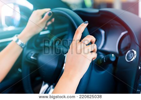 Closeup view of a woman's driver hands holding a steering wheel of a modern luxury car